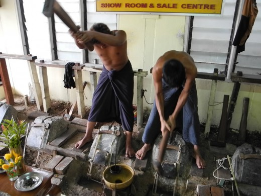 While the women prepare the gold leaf, the men are pounding it. The bucket of water in front of them is their timer; when the ladle sinks, they flip the stack of gold leaves and pound the other side.