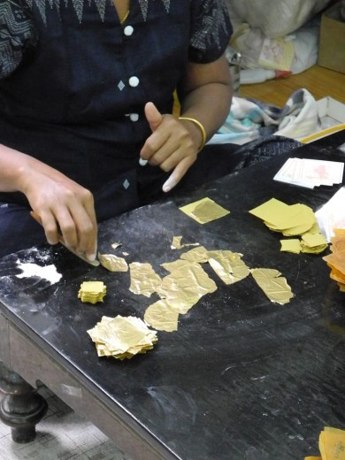 Women preparing gold leaf for sale in a sealed room in Mandalay's Gold Pounders' District.