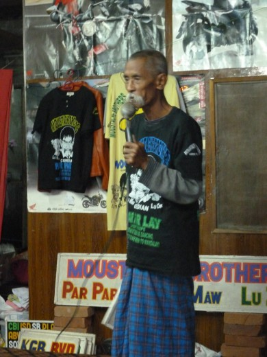 Lu Maw, the only one of the Moustache Brothers with passable English, cracks some jokes.