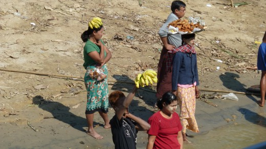 Fruit vendors try to sell food along the shore